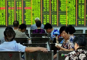 Investidores acompanham o resultado do mercado acionário na China Foto: CHINA DAILY / REUTERS