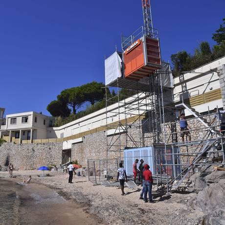 Trabalhadores desmontam um elevador temporário na praia de Mirandole, localizado abaixo de uma mansão de propriedade da família real saudita em Golfe Juan Vallauris, no sudeste da França Foto: Bruno Bebert / AP