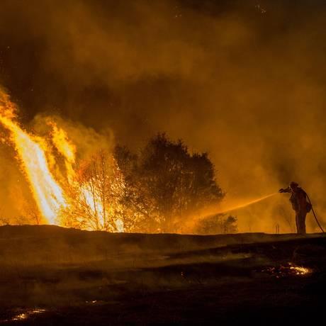Bombeiro combate incêndio perto de Clearlake, na Califórnia Foto: Josh Edelson / AFP