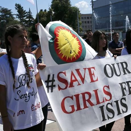 Em Genebra, em frente à sede das Nações Unidas, mulheres carregam faixa pedindo proteção de meninas contra Estado Islâmico Foto: DENIS BALIBOUSE / REUTERS