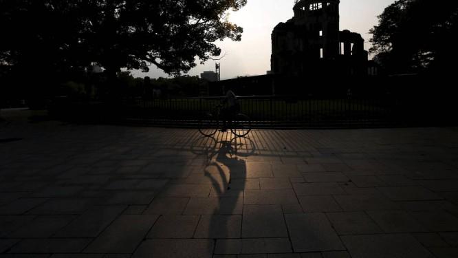 Morador passeia de bicicleta ao lado da Cúpula da Bomba Atômica em Hiroshima Foto: ISSEI KATO / REUTERS