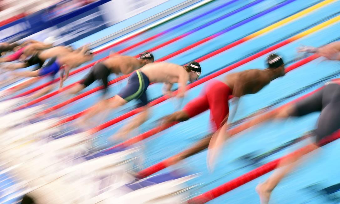 Nadadores saltam para uma das eliminatórias dos 50 metros peito MARTIN BUREAU / AFP
