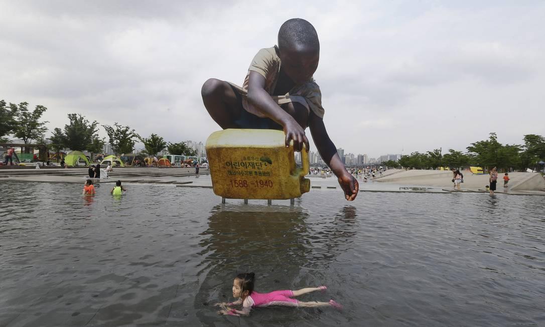 Garota se refresca em fonte para escapar do calor em Seul, onde a temperatura chegou aos 32 graus Ahn Young-joon / AP