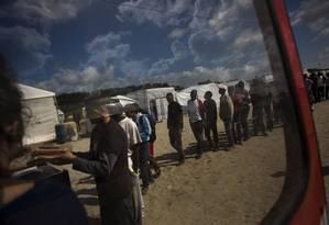 Imigrantes aguardam porção de comida distribuída em Calais, na França Foto: Emilio Morenatti / AP
