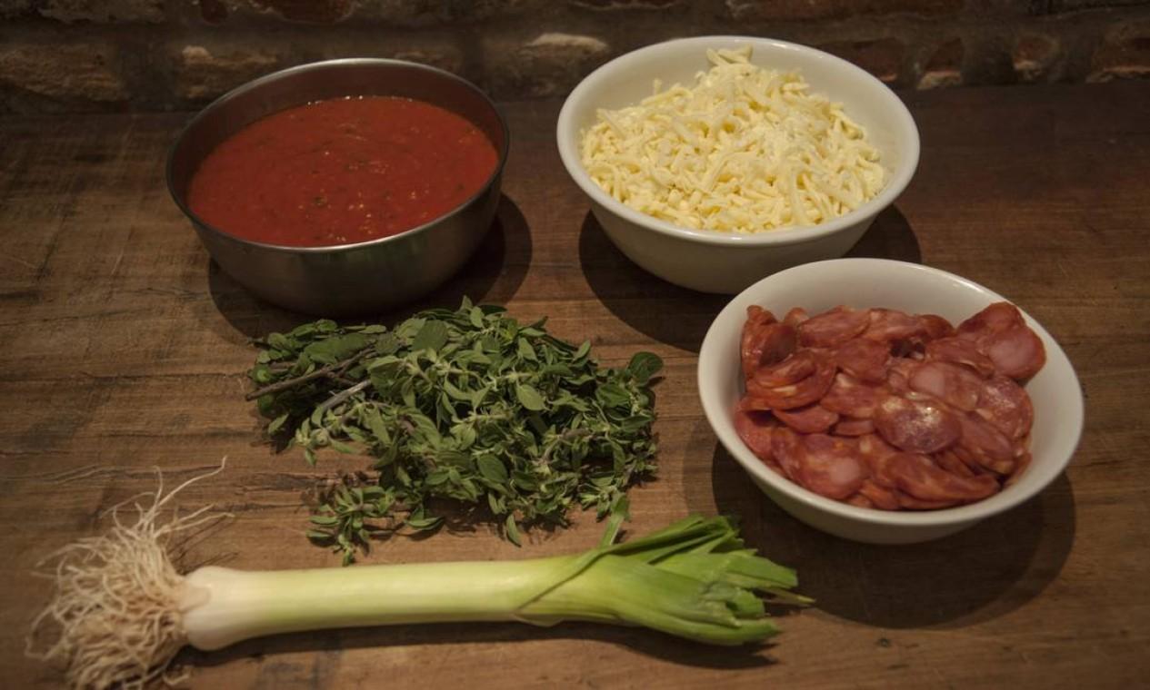 Separe os ingredientes da cobertura: mozzarella di búfala (150g), molho de tomate (150 ml), linguiça artesanal de lombo suíno (150g), 1 talo de alho poró, orégano fresco. Foto: Adriana Lorete / O Globo