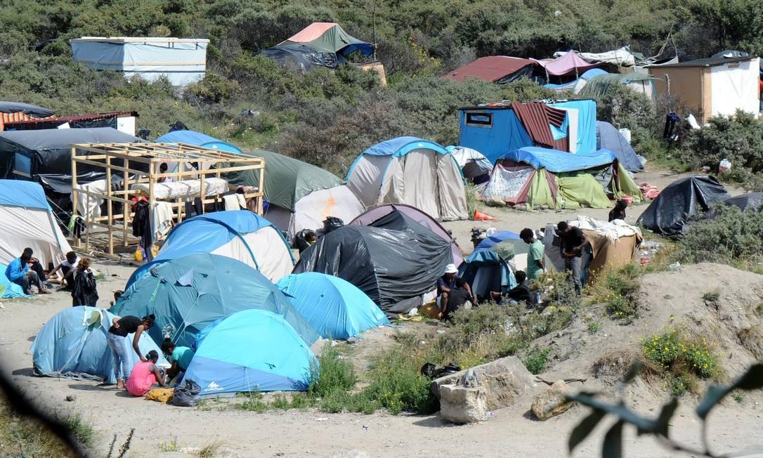Acomodados em tendas e barracas, imigrantes ilegais tocam seus afazeres no maior campo de refugiados de Calais, na França, à espera de uma chance de atravessar o Eurotúnel e buscar uma nova vida no Reino Unido Foto: FRANCOIS LO PRESTI/AFP