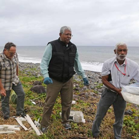 Um especialista da Malásia (centro) procura os restos do voo MH370 em uma praia em Saint-Andre na Ilha Reunião, em 4 de agosto de 2015 Foto: RICHARD BOUHET / AFP