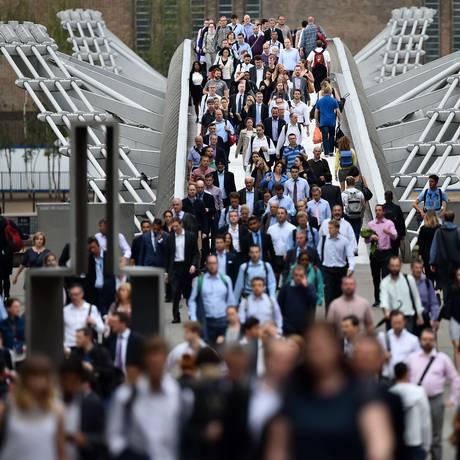 Transeuntes atravessam o rio Tâmisa em passarela, enquanto greve atinge a hora do rush no metrô de Londres Foto: BEN STANSALL;BEN STANSALL / AFP