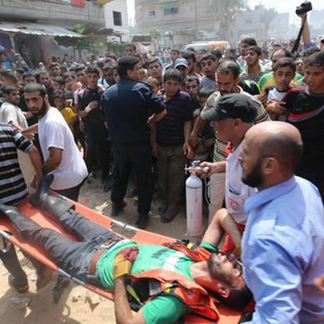 Palestino, que ficou ferido na explosão em Rafah, é transportado em maca para a ambulância Foto: Ibraheem Abu Mustafa / Reuters
