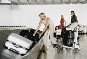 Passageiros aguardam a bagagem na esteira do aeroporto. Foto: Digital Vision / Divulgação