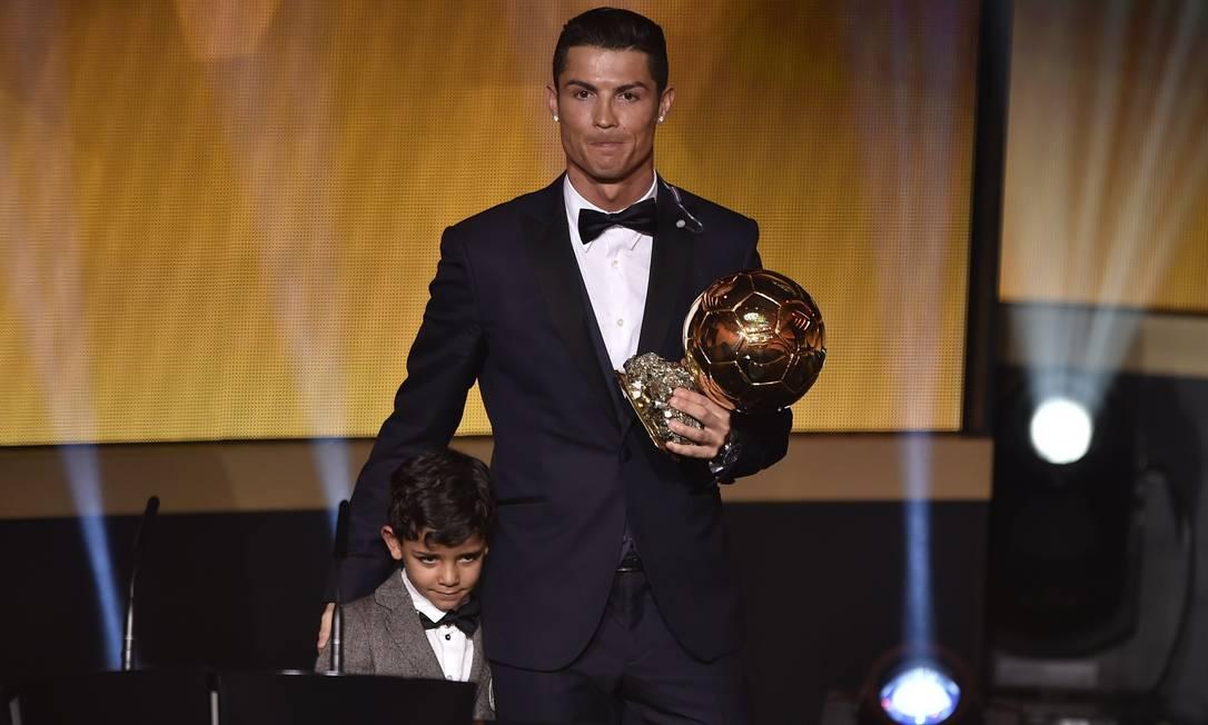 Cristiano Ronaldo é outro que baba a sua cria: na foto, o jogador segura a Bola de Ouro ao lado do filho durante a premiação em Zurique FABRICE COFFRINI / AFP