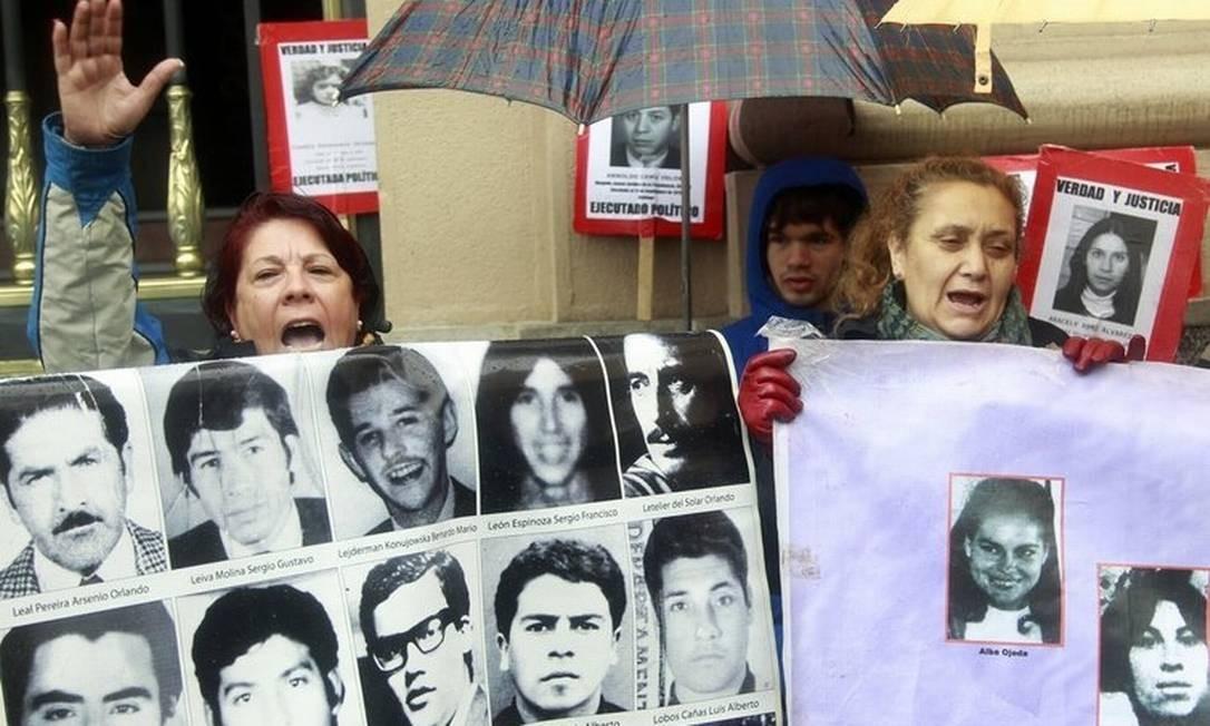 Festa. Chilenos comemoram segurando retratos de vítimas da ditadura Foto: Claudio Reyes/AFP