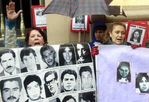 Festa. Chilenos comemoram a morte do general Manuel Contreras, chefe da polícia secreta da ditadura, segurando retratos de vítimas do regime militar Foto: Claudio Reyes/AFP