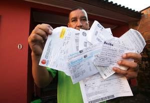 Inadimplente. Elias mostra as contas que não teve como pagar Foto: Gabriela Di Bella