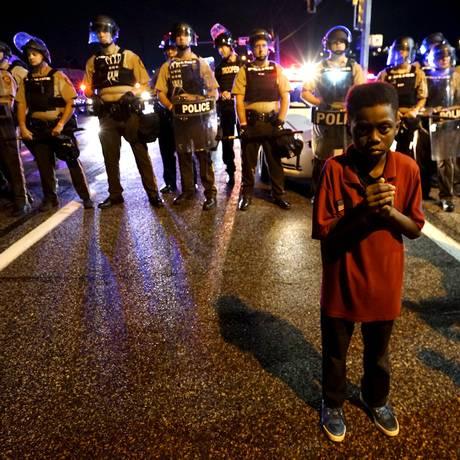 Amarion Allen, de 11 anos, em frente a linha de polícia pouco antes da troca de tiros entre a polícia e manifestantes em protestos por um ano da morte de Michael Brown Foto: RICK WILKING / REUTERS