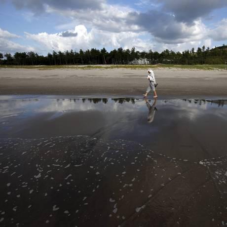 Shouhei Nomura, 79 anos, confere níveis de radiação enquanto caminha por praia de Satsumasendai Foto: ISSEI KATO / REUTERS