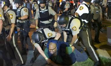Manifestante é preso durante um protesto que marca o aniversário de um ano da morte de Michael Brown na rua West Florrisant, em Ferguson Foto: SCOTT OLSON / AFP