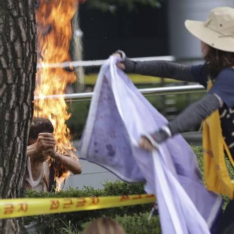 Mulher tenta ajudar homem que ateou fogo no próprio corpo em Seul, na Coreia do Sul Foto: Lee Jin-man / AP