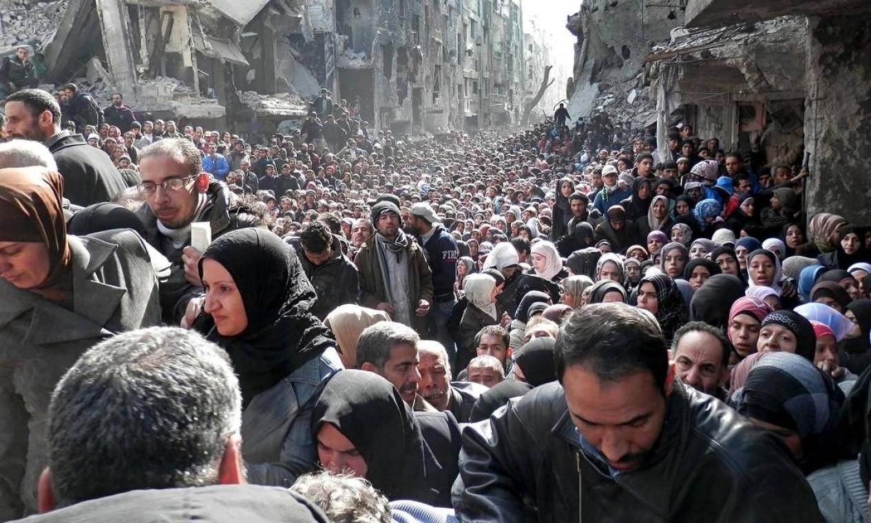 Fila de refugiados palestinos se forma no campo de Yarmouk, em Damasco, para receber ajuda humanitária em 2015 Foto: UNRWA / AP