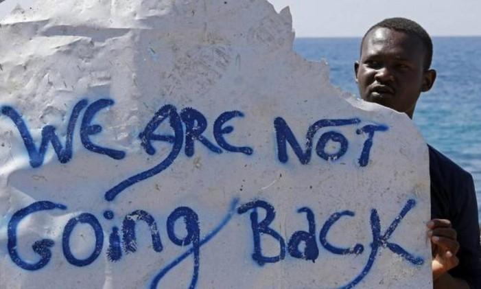 Migrante exibe cartaz ao chegar na Itália Foto: © Eric Gaillard / Reuters / REUTERS