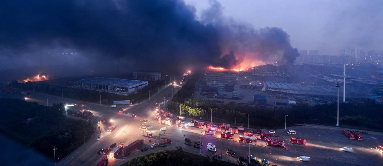 Fogo e fumaça sobe no local das explosões em Tianjin Foto: STR / AFP