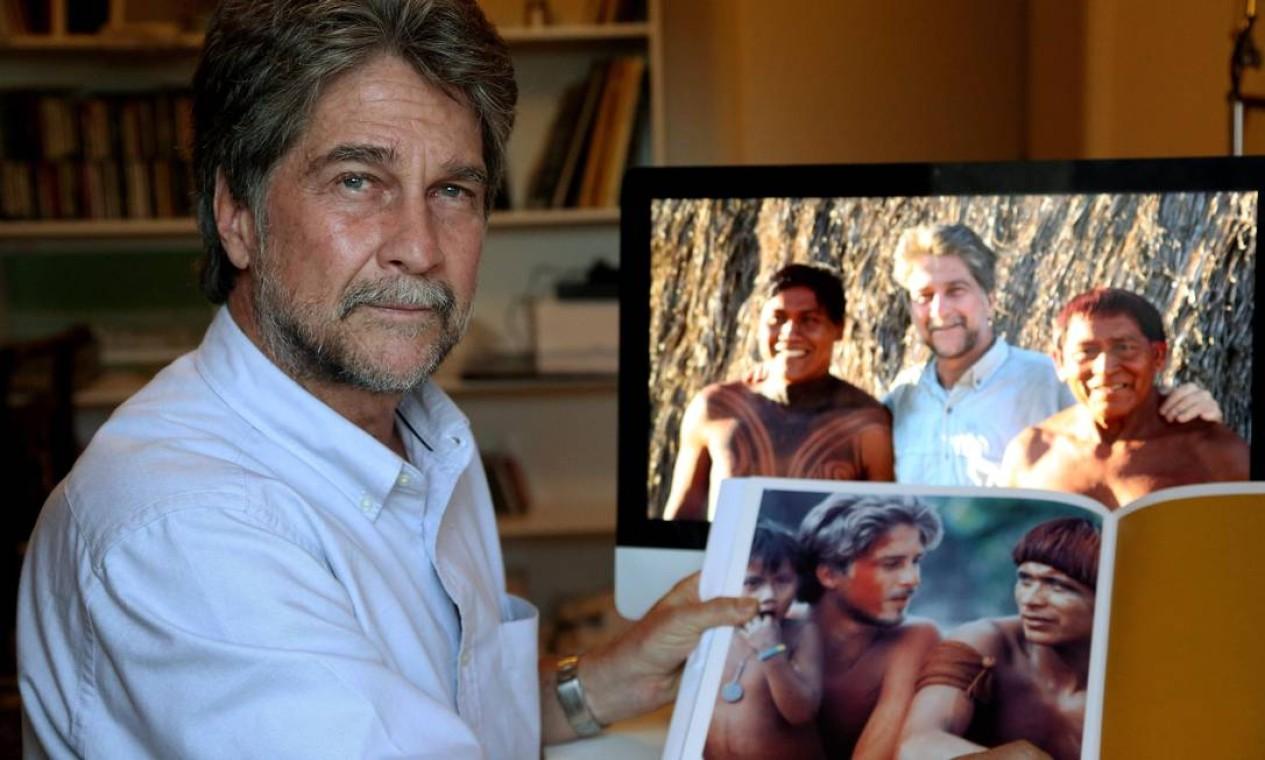 No apartamento em que mora no Leblon, Joãozinho mostra as imagens feitas no Xingu em 1978 e este ano Foto: Custódio Coimbra / Agência O Globo