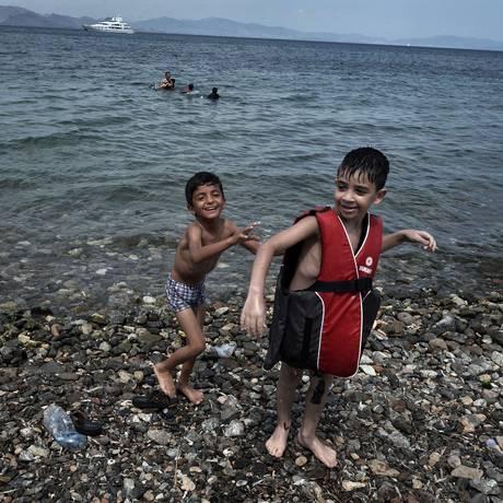 Na ilha grega de Kos, onde a chegada de refugiados sírios têm sido incontrolável, crianças brincam em praia Foto: LOUISA GOULIAMAKI / AFP