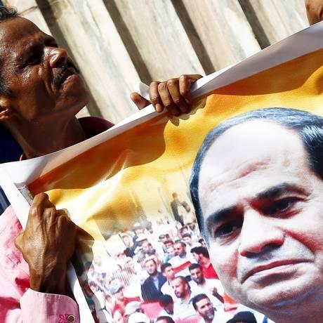 Egípcio carrega foto do presidente Sisi: figura do ex-general, que se promove como comandante de nação em desenvolvimento, é onipresente Foto: Amr Abdallah Dalsh / REUTERS/ 10-8-2015