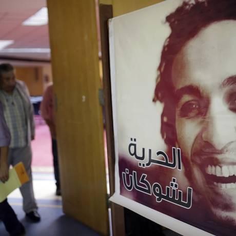 Repórteres passam ao lado de um poster com o rosto do fotojornalista egípcio Mahmoud Abou-Zeid, preso há mais de 700 dias sem qualquer acusação Foto: Amr Nabil / AP/12-8-2015
