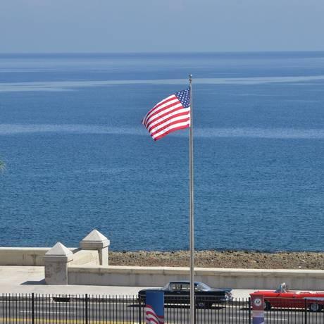 A bandeira americana na embaixada em Havana e carros antigos ao fundo Foto: REUTERS