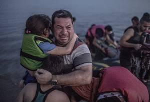 Um refugiado sírio abraça os dois filhos e chora ao conseguir desembarcar na ilha de Kos, na Grécia, após a travessia em um barco inflável: € 1.160 por pessoa Foto: DANIEL ETTER / NYT