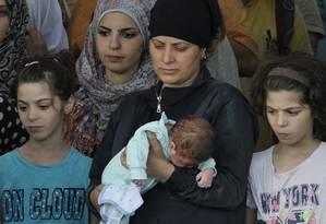 Mulheres aguardam para desembarcar em Siracusa: quem viaja sozinha é alvo mais fácil de gangues Foto: Carmelo Imbesi / AP