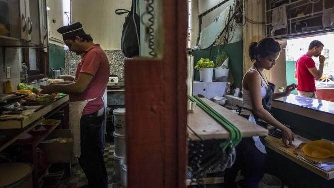 Jovens preparam hambúrgueres e pizzas em restaurante privado de Havana Foto: MERIDITH KOHUT / NYT