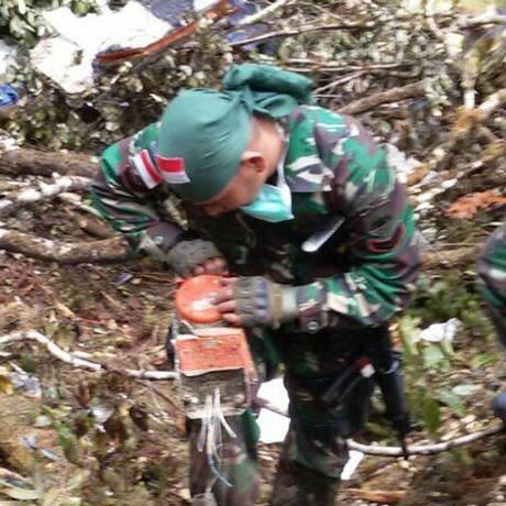 Foto divulgada pelo Exército indonésio mostra um soldado recuperando a caixa-preta do avião da Trigana Air Foto: INDONESIAN ARMY / AFP