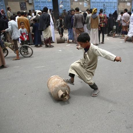 Em Sanaa, menino precisa rolar botijão com os pés após esperar por horas em fila para comprar gás Foto: Hani Mohammed / AP