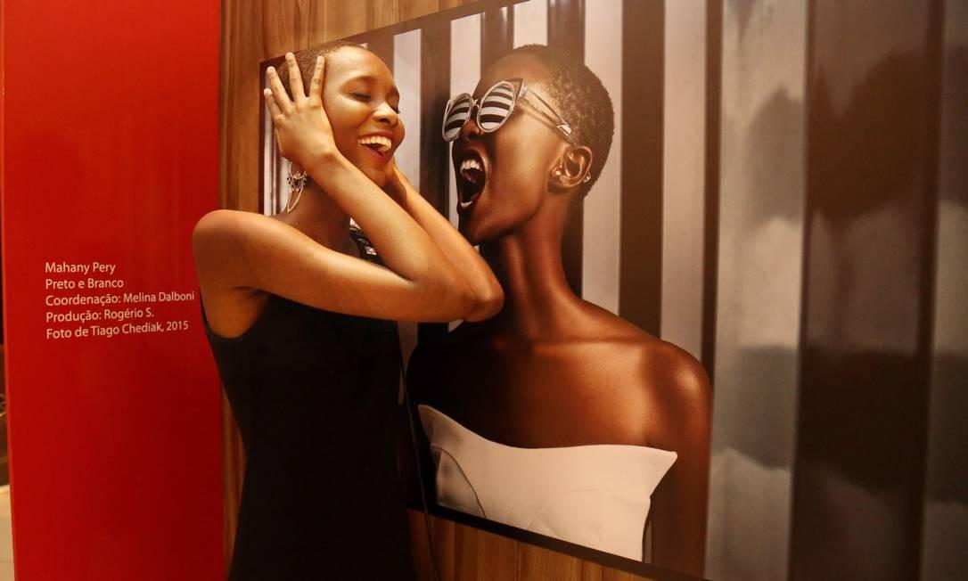 A modelo Mahany Pery brinca com a sua foto na exposição Foto: Marcos Ramos / Agência O Globo