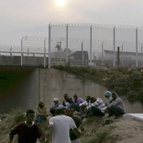 """Imigrantes se reúnem perto de acampamento improvisado chamado """"A Nova Selva"""" Foto: REGIS DUVIGNAU / REUTERS"""