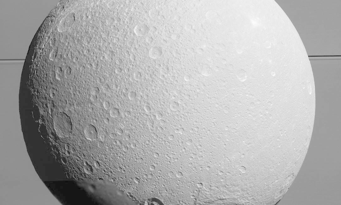 Dione vista pela Cassini durante a aproximação de segunda-feira, no quinto e último sobrevoo da sonda por esta lua de Saturno, ao fundo com seus anéis, em missão que já dura mais de dez anos Foto: Nasa/JPL-Caltech/Space Science Institute