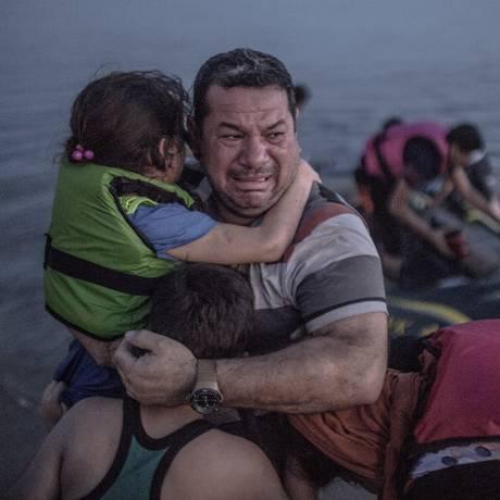 Mais que mil palavras. Refugiado sírio Latih Majid, em prantos, abraça filha ao chegar à Grécia Foto: DANIEL ETTER/The New York Times