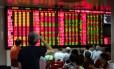 Investidores monitoram as telas que mostram os movimentos do mercado financeiro em Xangai