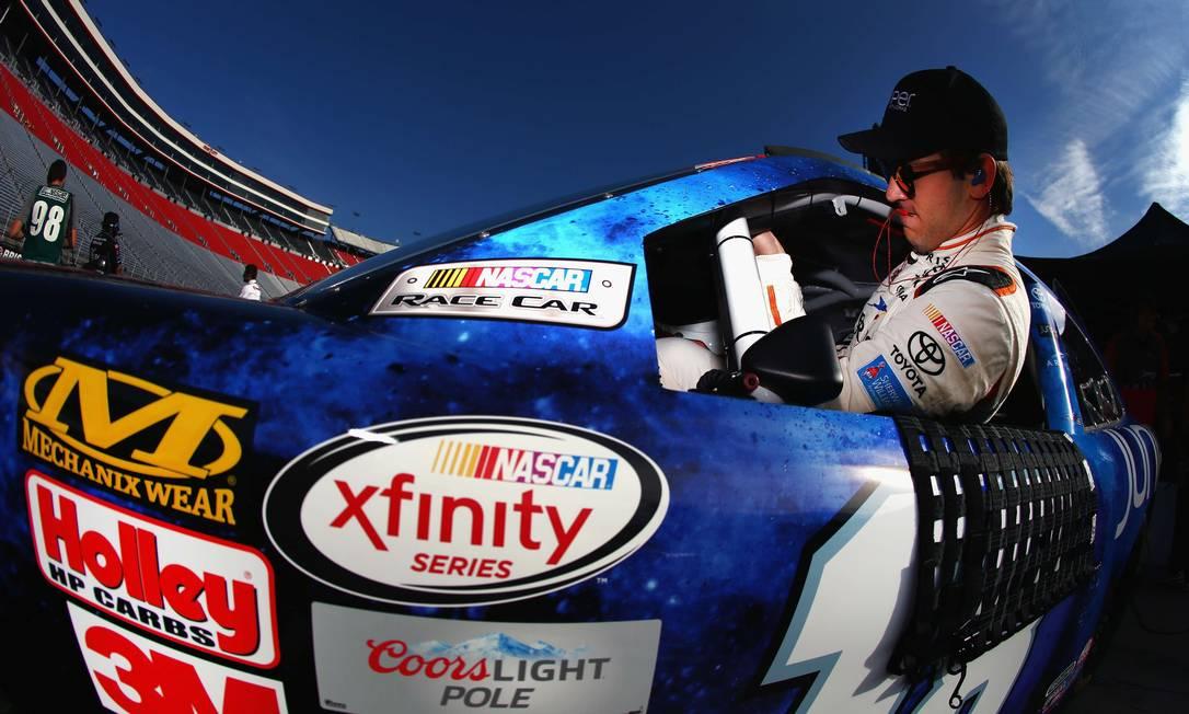 Daniel Suarez, piloto do carro #18, Juniper Toyota, se acomoda no cockpit para o treino de NASCAR XFINITY Series em Bristol, Tennessee. TOM PENNINGTON / AFP