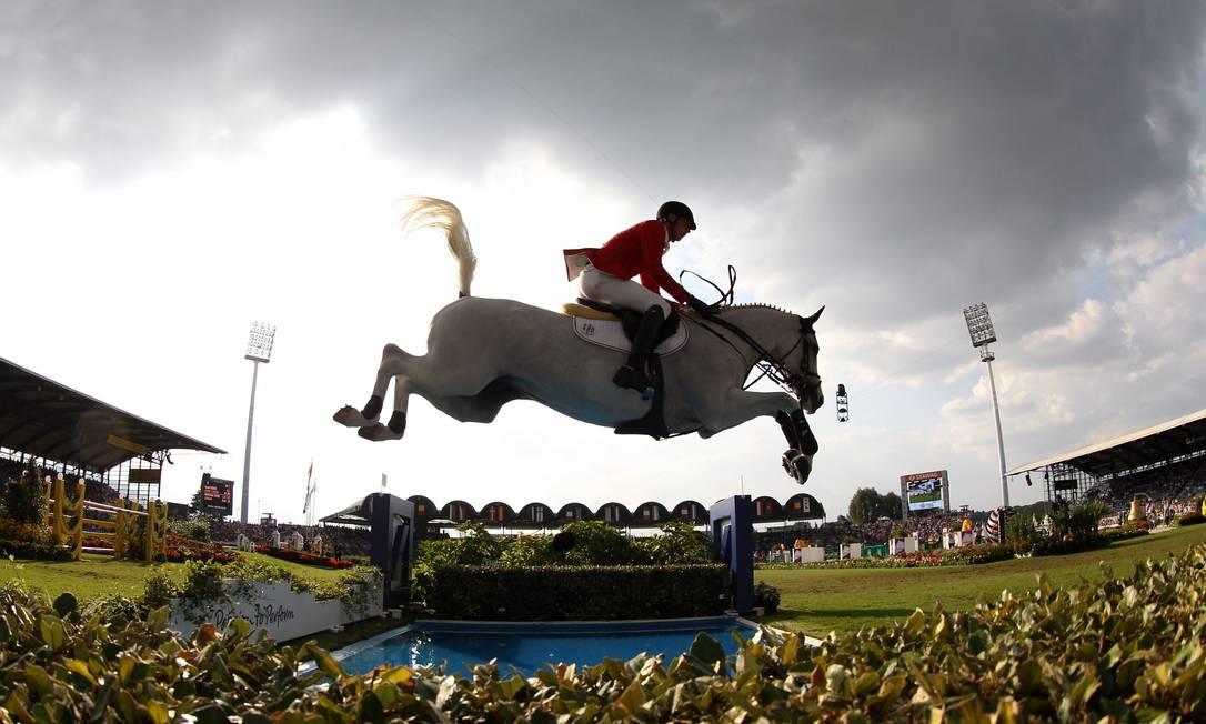 """O conjunto do cavaleiro Daniel Deusser e seu cavalo """"Cornet d'Amour"""", da Alemanha salta um obstáculo no campeonato europeu de equitação em Aachen, Alemanha FRISO GENTSCH / AFP"""