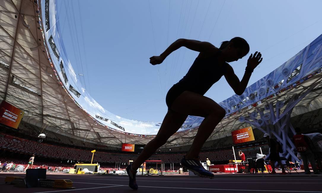 """Atleta treina para o campeonato mundial de atletismo no """"ninho do pássaro"""", estádio nacional da China em Pequim ADRIAN DENNIS / AFP"""