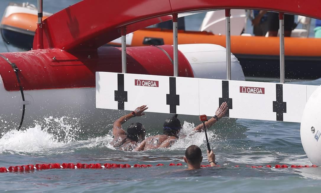 O brasileiro Allan do Carmo e o japonês Yasunari Hirai chegam praticamente juntos aopos os 10km da prova maeculina do evento-teste de maratona aquática na Praia de Copacabana Alexandre Cassiano / Agência O Globo