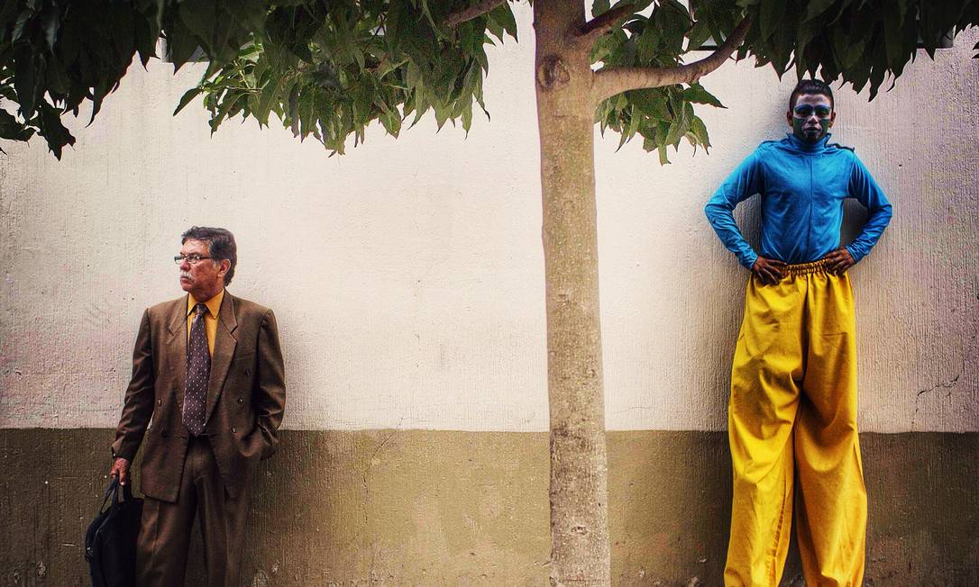 Everyday Latin America. Artista de rua descansa ao lado de um engravatado durante uma passeata documentada pelo guatemalteco Saul Martinez, em junho. Foto: Wenbin Wu / Reprodução