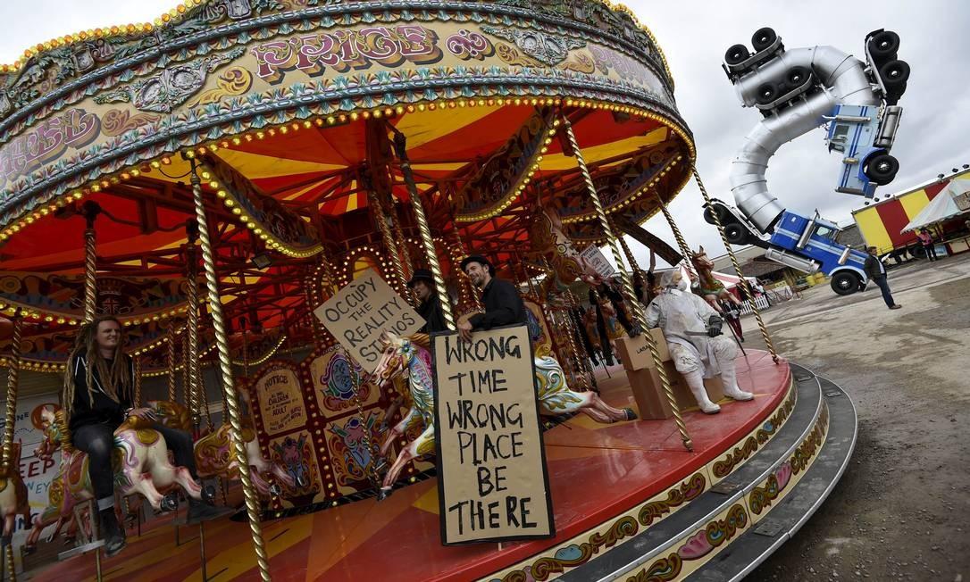 Pessoas andam no carrossel de 'Dismaland', o parque temático com instalações criadas pelo misterioso grafiteiro superstar Banksy e por 56 artistas-plásticos convidados Foto: TOBY MELVILLE / Reuters