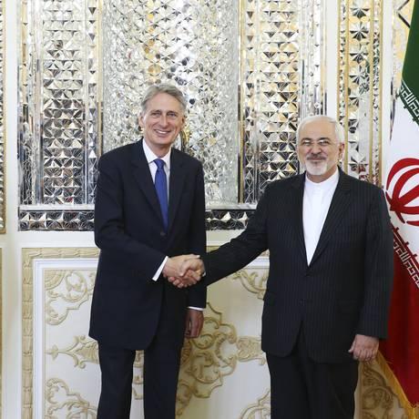 À direita, o ministro do exterior do Irã Mohammad Javad Zarif cumprimenta o secretário britânico do exterior Philip Hammond perante a mídia antes de seu encontro em Teerã, no Irã, no domingo, 23 de agosto de 2015 Foto: Vahid Salemi / AP