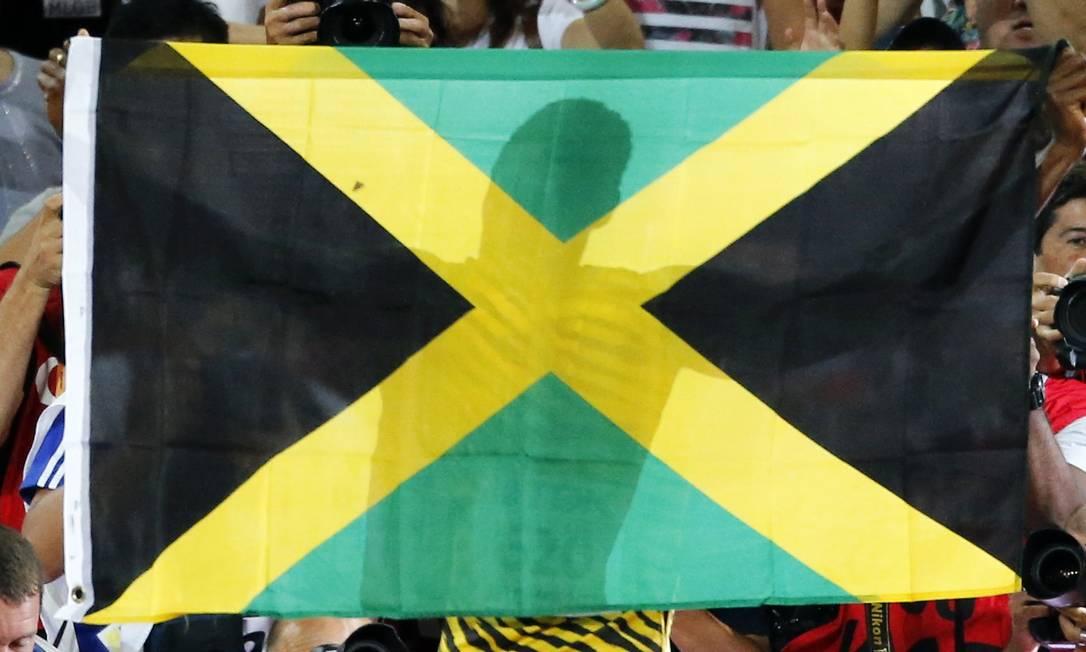 Usain Bolt celebra com a bandeira da Jamaica a vitória dos 100m rasos no campeonato Mundial de Atletismo, no estádio nacional Ninho do Pássaro, em Pequim FABRIZIO BENSCH / REUTERS