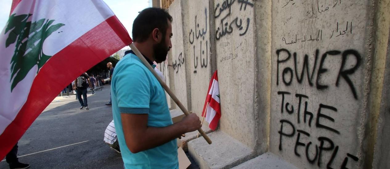 Manifestante se vê diante de pichação pedindo poder para o povo, como na música de John Lennon Foto: - / AFP