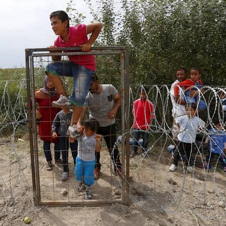 Com barreira ainda sob construção, refugiados sírios atravessam para a Hungria Foto: LASZLO BALOGH / REUTERS